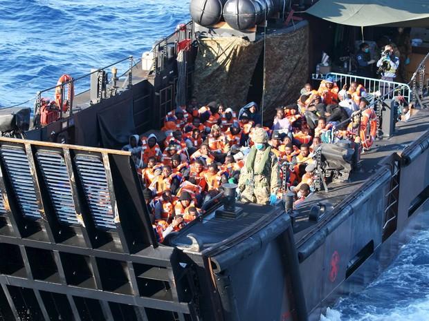Migrantes resgatados no Mar Mediterrâneo são levados a terra firme na barcaça de desembarque militar HSM Bulmark (Foto: Jamie Weller/Crown Copyright/Reuters)