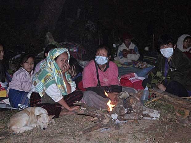 Refugiados esperam na estrada, após campo onde viviam pegar fogo. (Foto: Wichai Taprieu / AP Photo)