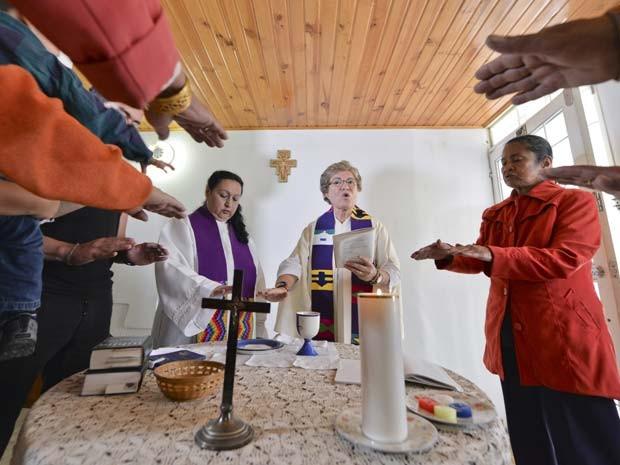 Olga Lucia Alvarez (direita), com assistência de Aida Soto (esquerda), realiza uma missa em Bogotá no dia 22 de março (Foto: AFP PHOTO/Luis Acosta)