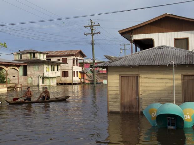 Moradores usam um barco para se locomover em Anamã, no Amazonas (Foto: Bruno Kelly/Reuters)