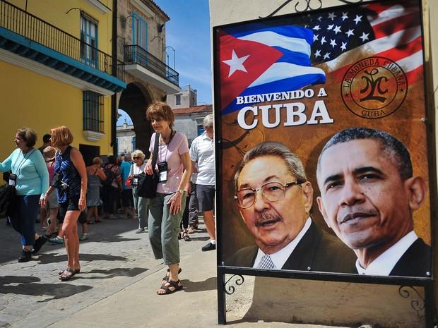 Cartaz com foto de Barakc Obama e Raúl Castro é visto nesta quinta-feira (17) em Havana, dias antes da chegada do presidente americano a Cuba (Foto: YAMIL LAGE / AFP)