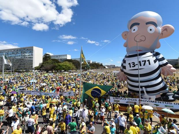 BRASÍLIA - Boneco inflávio do ex-presidente Lula com uniforme de presidiário é visto durante manifestação em frente ao Congresso Nacional, em Brasília (Foto: Evaristo Sa/AFP)