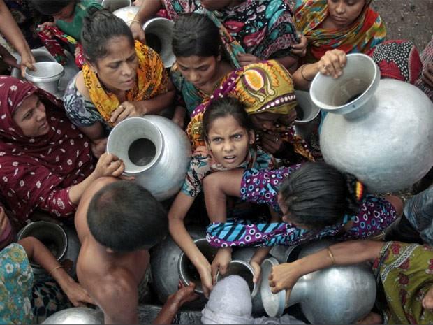 Pessoas se acotovelam para receber água em Dacca, capital de Bangladesh. (Foto: Reuters)