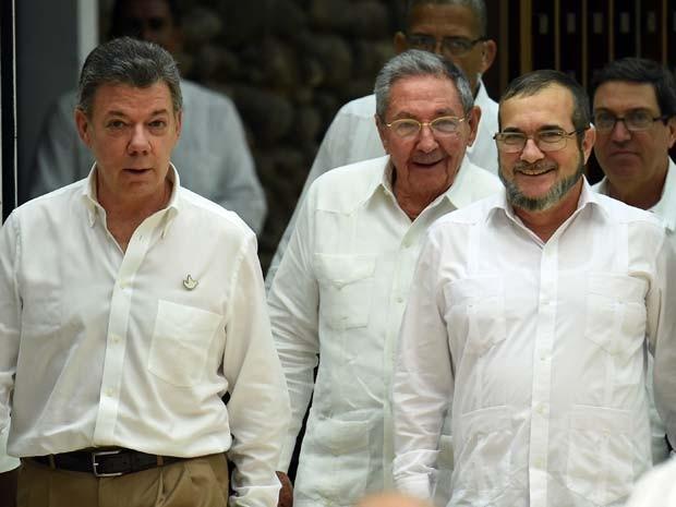 Os presidentes da Colômbia Juan Manuel Santos (esquerda), de Cuba, Raúl Castro (centro) e o líder das Farc, Timoleon Jimenez, chegam para reunião em Havana nesta quartafeira (23)  (Foto: AFP PHOTO / LUIS ACOSTA)
