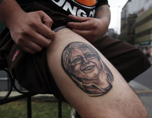 Apoiador da ex-presidente Michelle Bachelet mostra nova tatuagem com o rosto dela, que nestas eleições concorre à presidência. (Foto: Luis Hidalgo/AP Photo)