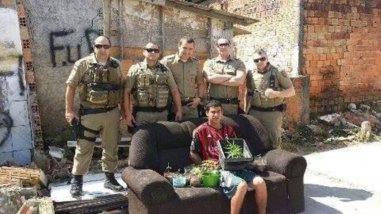 Policiais tiraram foto com jovem segurando maconha  (Foto: Reprodução/Facebook)