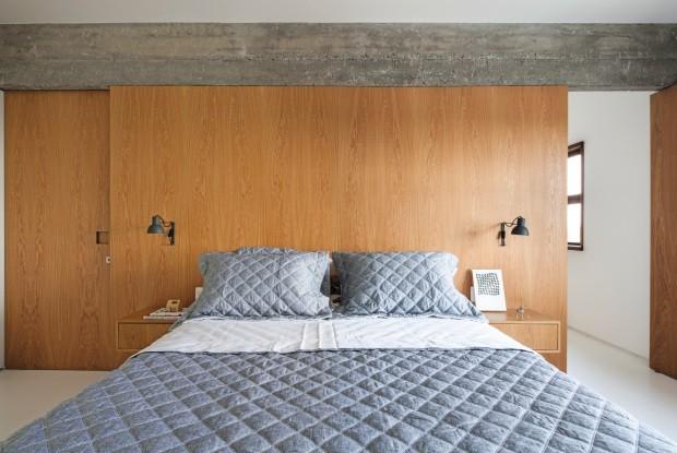 Quarto. A parede revestida de carvalho-americano traz calor ao espaço. Sobre a cama, roupa da Trousseau; nas laterais, luminárias da Reka (Foto: Maíra Acayaba / Editora Globo)