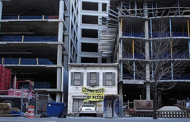 Entre dois prédios em construção, uma pequena casa, em Washington, nos Estados Unidos. Os proprietários acabaram desistindo de morar lá e transformaram o local em pizzaria (Foto: Reprodução/Hypeness)