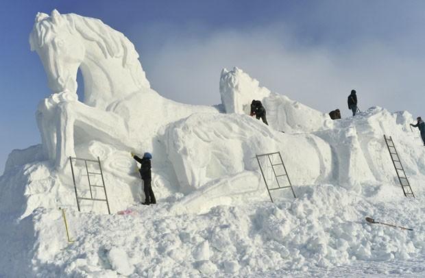 Chineses são vistos esculpindo esculturas de gelo no formato de cavalo (Foto: China Daily/Reuters)