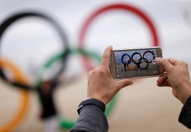 Mulher tira foto dos aneis olímpicos na praia de Copacabana antes do início dos Jogos Olímpicos Rio 2016 (Foto: Ueslei Marcelino/Reuters)
