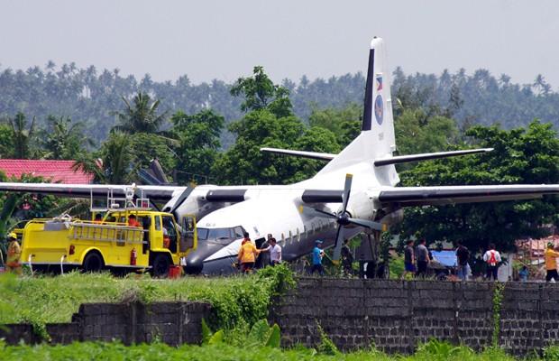 Pessoas se reúnem em volta do Fokker F27 da Força Aérea filipina nesta segunda-feira (11), após acidente sem feridos (Foto: Ramon Marbella/Reuters)