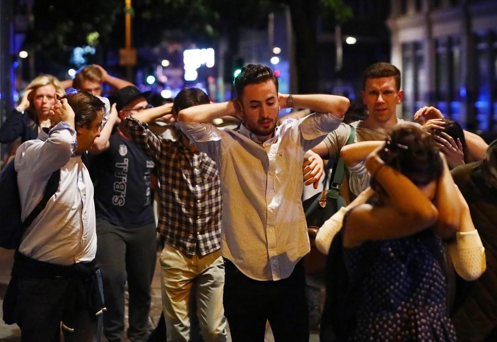 Pessoas saem da área próxima a London Bridge com as mãos na cabeça (Foto: REUTERS/Neil Hall )