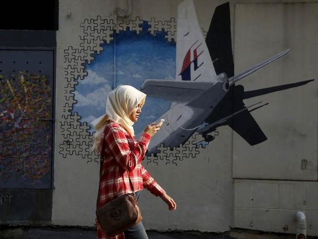 Mulher passa mexendo em seu smartphone em frente a um mural de grafite com o avião desaparecido há 2 anos do voo MH370 da Malaysia Airlines, em Kuala Lumpur, na Malásia (Foto: Olivia Harris/Reuters)