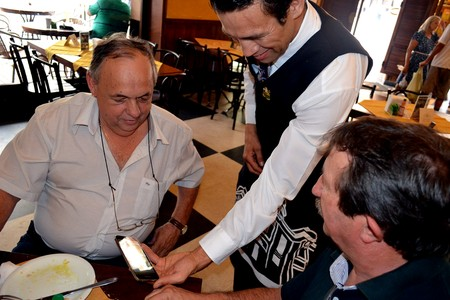 Alessandro Flor mostra vídeo das suas lutas para os clientes (Foto: Cleber Akamine)