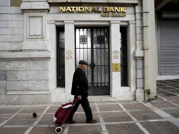 Homem caminha em frente a agência bancária em Atenas, Grécia, neste sábado (31) (Foto: REUTERS/Michalis Karagiannis)