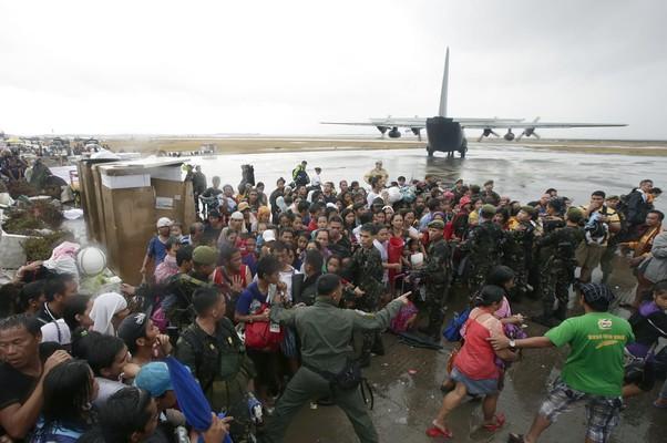 Sobreviventes do tufão Haiyan se aglomeram para embarcar em um avião das Forças Aéreas das Filipinas para saírem da cidade da Tacloban, a mais devastada do país. Autoridades estimam que mais de 10 mil pessoas morreram (Foto: AP Photo/Bullit Marquez)