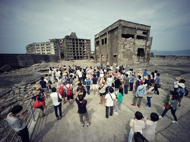 Turistas visitam uma parte da ilha de Hashima, no sul do Japão. Uma comissão especial da UNESCO a declarou Patrimônio Mundial. (Foto: Eugene Hoshiko/AP Photo)