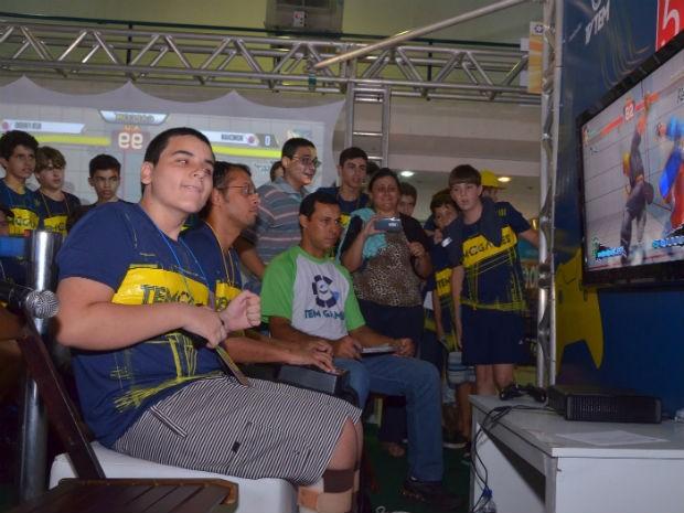 Ângela filma o filho jogar enquanto outros competidores acompanham a luta  (Foto: Fábio Molina/Arquivo pessoal)