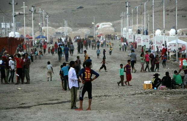 Refugiados sírios-curdos caminham pelo campo de Quru Gusik, na região curda do norte do Iraque, em 27 de agosto (Foto: Safin Hamed/AFP)