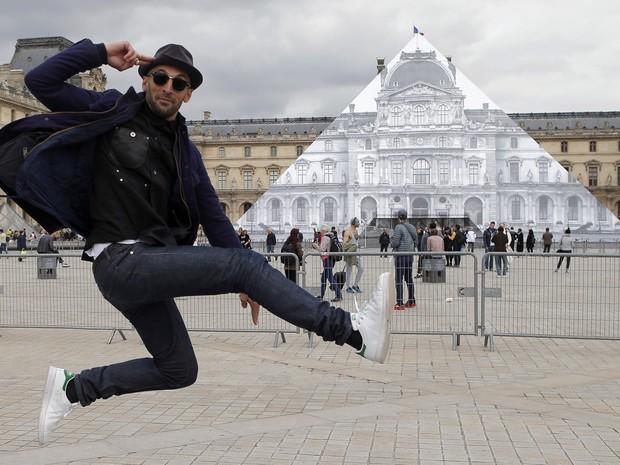 O artista de rua JR salta em frente à pirâmide do museu do Louvre em Paris, na França, exposta com seu último trabalho (Foto: François Mori/AP)