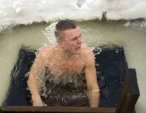 Participante da maratona de saunas entra em buraco de gelo, na Estônia. (Foto: Raigo Pajula/AFP)