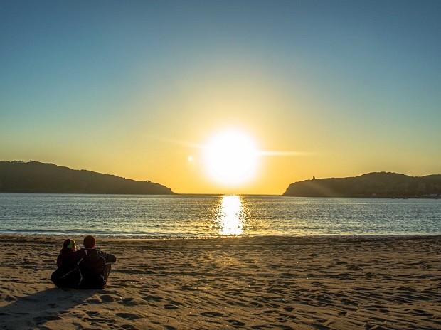 A publicitária Julie Assêncio e o administrador de redes Thiago Ruiz veem o pôr do sol em praia de Portugal (Foto: Diocá/Divulgação)