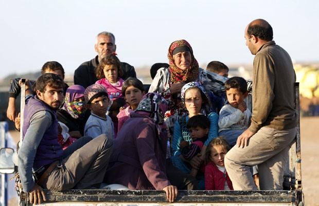 Refugiados sírios curdos chegam à Turquia após deixarem a cidade de Kobane nesta segunda-feira (6) (Foto: Umit Bektas/Reuters)