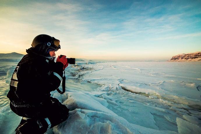 Fotógrafo prepara clique no arquipélago de Svalbard, na Noruega, durante expedição de Marco Brotto — muita gente faz o roteiro da aurora apenas para fotografar (Foto: Divulgação)