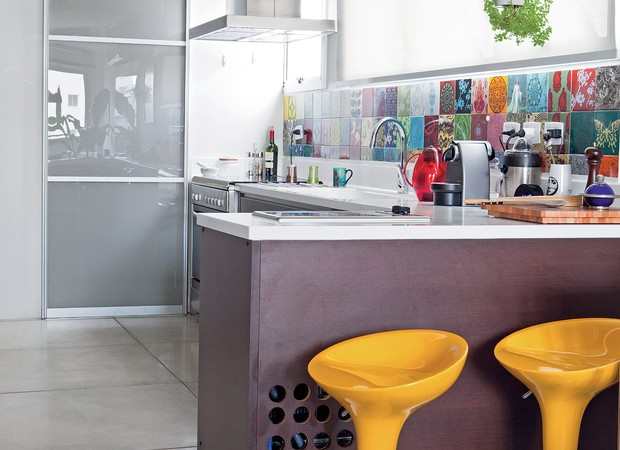 os azulejos estampados, da calu Fontes, eoamarelo vibrante das banquetas, da Maria Jovem, deixam a cozinha divertida. os furos embaixo da bancada são o respiro para a máquina de gelo. (Foto: Lufe Gomes)