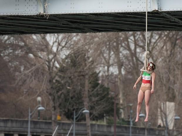 A ativista do Femen Sarah Constantin fez protesto com enforcamento simbólico contra o presidente do Irã em visita dele a Paris (Foto: Zacharie Scheurer/AP)