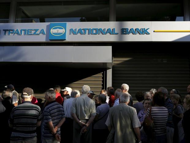 Pensionistas são vistos em frente a agência do Banco Nacional da Grécia fechada nesta segunda-feira (29), em Atenas  (Foto: REUTERS/Yannis Behrakis)