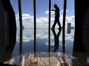 Homem caminha pelo piso de vidro construído no 37º andar da CCTV, a Televisão Central da China, no distrito central de negócios de Pequim (Foto: Jason Lee/Reuters)