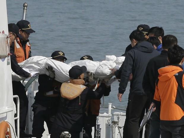 Corpo de passageiro de balsa que naufragou na Coreia do Sul é carregado por equipes de resgate no Porto de  Jindo, no sul de Seul.  (Foto: Lee Jin-man/AP)