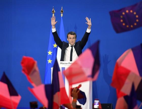 Emmanuel Macron, candidato a presidente na França, comemora chegada ao segundo turno. No fundo, uma bandeira da União Europeia. Macron é pró-UE (Foto:  FEFERBERG / AFP)