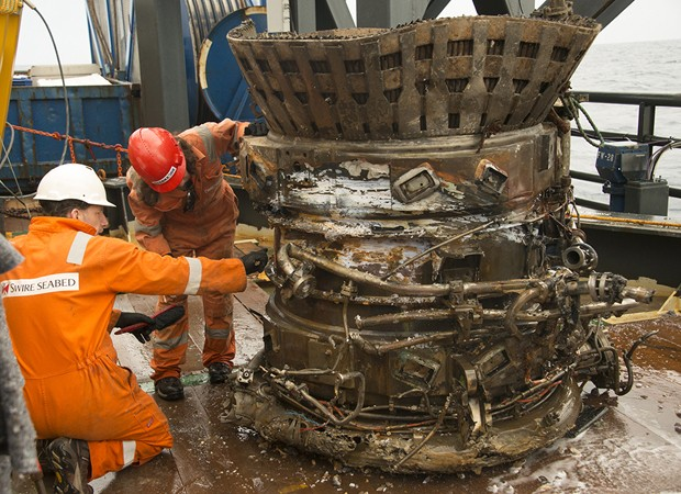 Técnicos inspecionam peça de motor da missão Apollo, resgatada a 4 km no fundo do mar (Foto: Bezos Expeditions/AP)