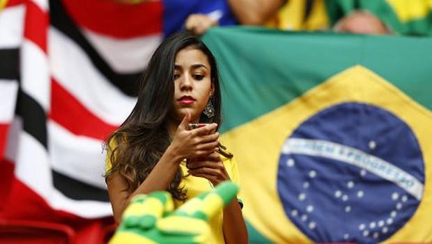Torcedora confere mensagem no celular durante a Copa do Mundo no Brasil ; geração Y no Brasil ; millenial ; tecnologia ; smartphone ;  (Foto: Dominic Ebenbichler/Reuters)