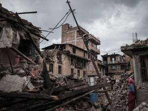 Mulher olha para edifícios danificados no Khokana, uma aldeia centenária nos arredores de Catmandu, no Nepal. Equipes de resgate correm contra o tempo para encontrar sobreviventes do terremoto que matou mais de 5 mil pessoas no sábado (25) (Foto: Philippe Lopez/AFP)