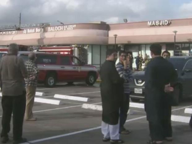 Pessoas observam a movimentação de bombeiros e investigadores após incêndio na  Sociedade Islâmica da Grande Houston  (Foto: CNN)
