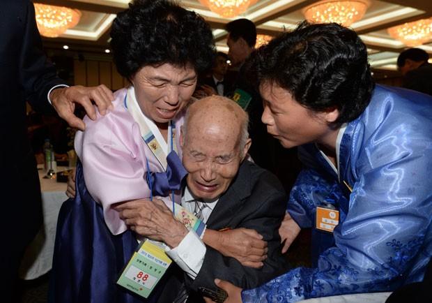 O norte-coreano Chae Hun-Sik, de 88 anos (no centro), encontra parentes sul-coreanos durante o reencontro (Foto: The Korea Press Photographers Association/AFP)