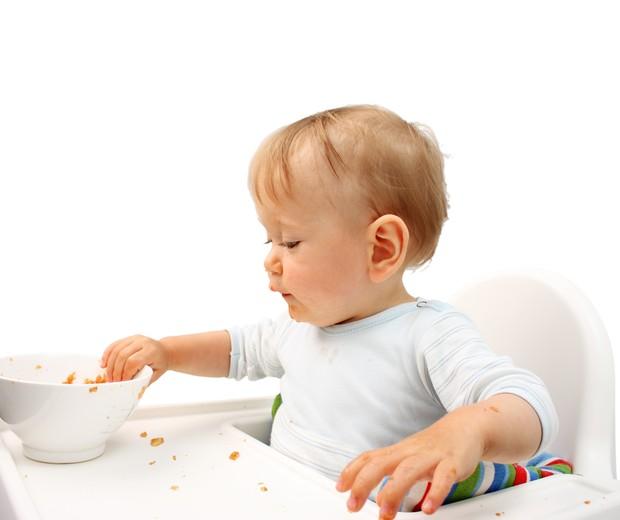 Criança com a mão na comida  (Foto: Thinkstock)