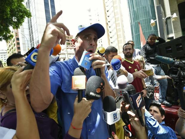 O líder opositor Henrique Capriles fala à imprensa durante protesto em frente ao Supremo Tribunal de Justiça nesta quarta-feira (25) em Caracas (Foto: JUAN BARRETO / AFP)