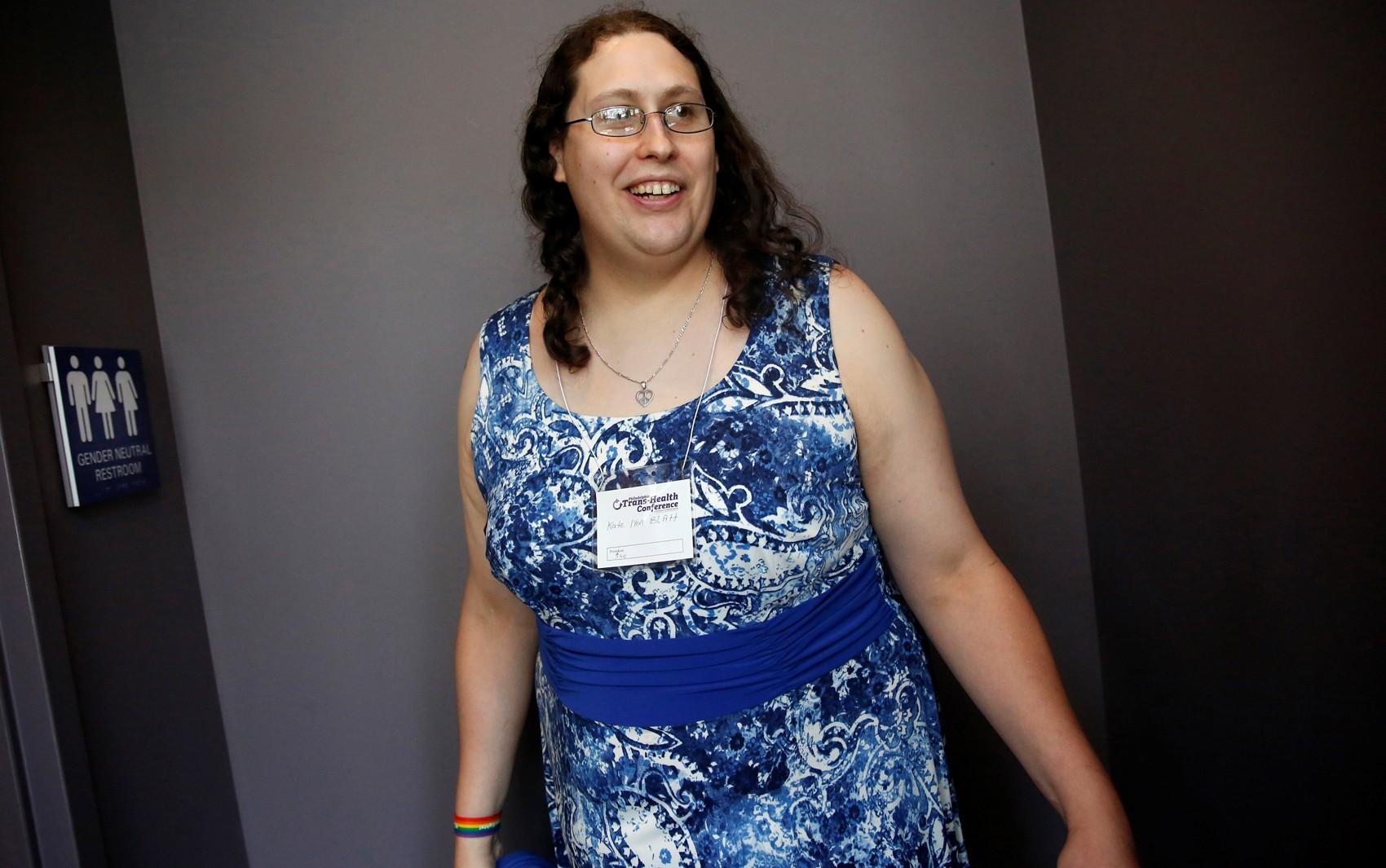 Kate Lynn Blatt, mulher transgênero, ao lado de banheiro de gênero neutro durante a 15ª Conferência Anual de Saúde Trans da Philadelphia, em 9 de junho (Foto: Reuters/Shannon Stapleton)