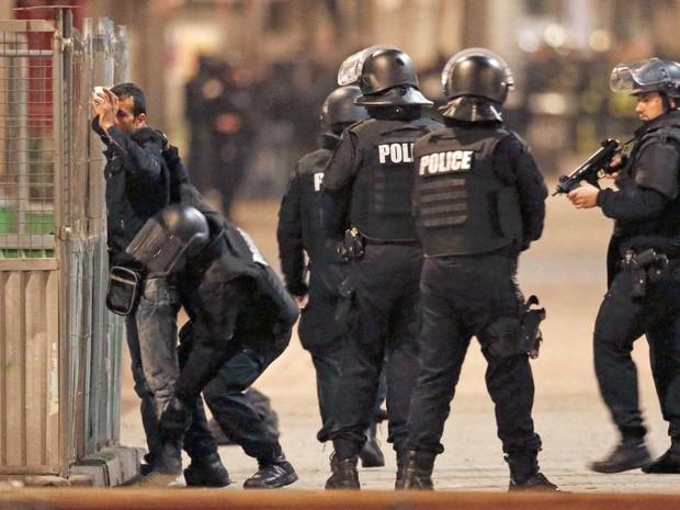 Polícia francesa revista um rapaz durante operação no norte de Paris (Foto: Christian Hartmann / Reuters)
