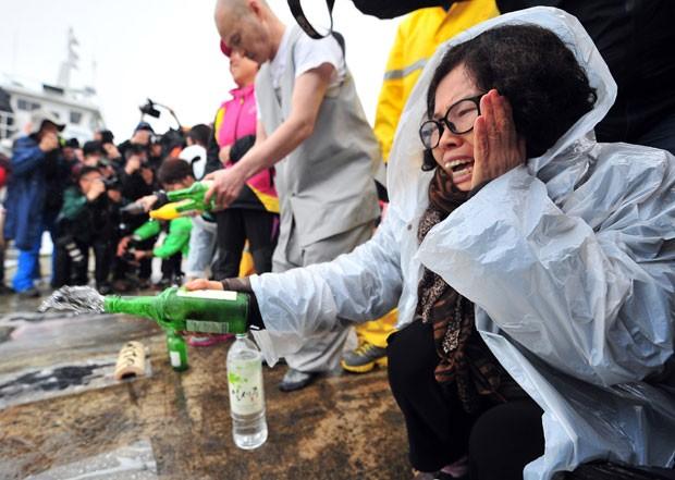 Mulher joga álcool no chão enquanto reza por passageiros desaparecidos da balsa 'Sewol' no porto de Jindo, na Coreia do Sul (Foto: Jung Yeon-Je/AFP)
