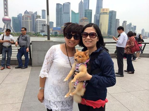 Correspondente da BBC (dir.) posa para foto com turista em Shangai: turista levava cachorro como se fosse um bebê 'humano' (Foto: BBC)