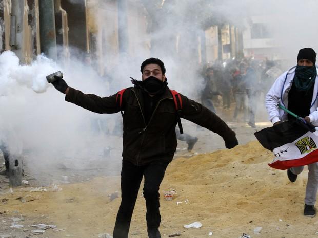 Manifestante se prepara para atirar bomba de gás lacrimogênio durante confornto no Cairo (Foto: Mohammed Abed/AFP)