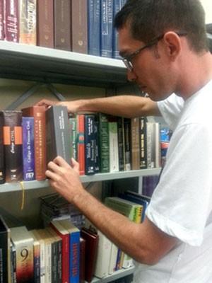 Ex-estudante de direito, o presidiário Carlos Anderson Aguiar escolhe um livro da área na estante do Núcleo de Ensino e Aprendizagem (Foto: Raquel Morais/G1)
