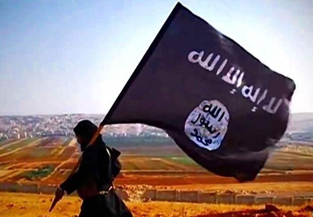 Militante carrega bandeira do Estado Islâmico (EI) : grupo coordena e lança ações terroristas (Foto: Reprodução/YouTube)