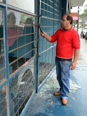 Mecânico Robson Sbravatti tirava os pedaços de vidro quebrado na manhã de quarta (26) (Foto: Leon Botão/G1)