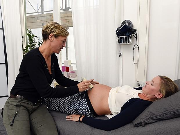 Parteira Sofie Laaftman (esq.) avalia saúde de Christina Singelman (Foto: Jonathan Nackstrand/AFP)